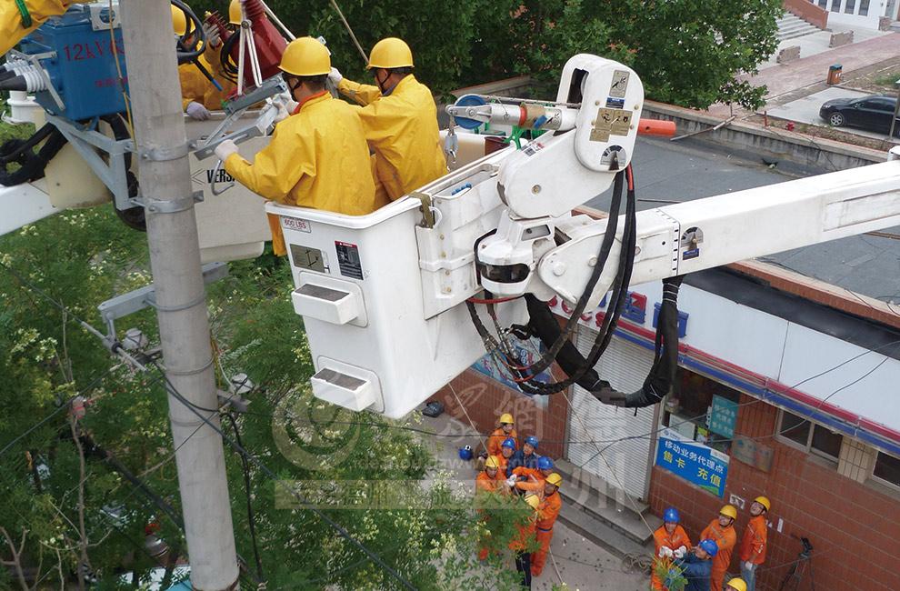 带电工作人员和现场作业人员合作,运用滑轮绳将新更换断路器转移至高空固定点.jpg