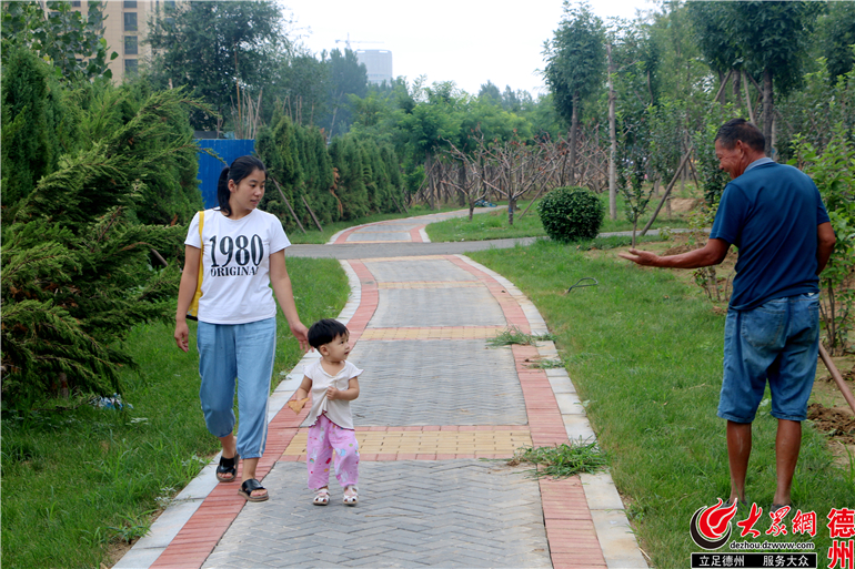 一位母亲带着孩子向风景区的工作人员问好